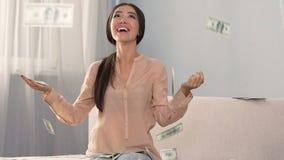 Porciones de efectivo que caen en la muchacha sorprendida feliz, términos de crédito bancario favorables, dinero almacen de metraje de vídeo