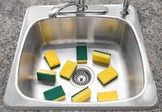 Porciones de esponjas amarillas en un fregadero de cocina limpio Fotos de archivo