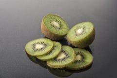 Porciones de fruta de kiwi en un fondo negro Imagen de archivo libre de regalías