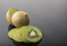 Porciones de fruta de kiwi en un fondo negro Fotografía de archivo libre de regalías