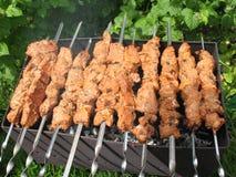 Porciones de kebabs en los pinchos a asar en la parrilla Imagenes de archivo