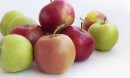 Porciones de manzanas rojas y verdes en el fondo blanco Fotos de archivo