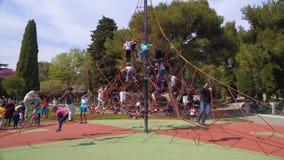 Porciones de niños felices que suben en el web de araña del cable en el parque de atracciones de los niños almacen de video