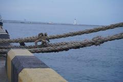 Porciones de nudos de la cuerda que llevan a las naves amarradas Cuerdas de barco, nave Amarrando el poste en la costa, elemento  imagen de archivo libre de regalías