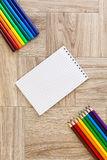 Porciones de rotuladores y de lápices de los colores variados con la libreta fotos de archivo