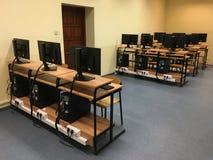 Porciones de tablas, de ordenadores y de monitores en la sala de clase vacía foto de archivo