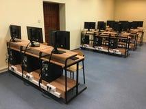Porciones de tablas, de ordenadores y de monitores en la sala de clase vacía imagen de archivo