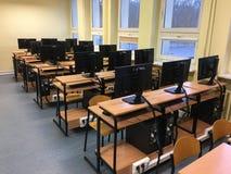 Porciones de tablas, de ordenadores y de monitores en la sala de clase vacía fotos de archivo libres de regalías