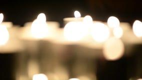 Porciones de velas que queman en la oscuridad Defocusing Luz blanca, bokeh metrajes