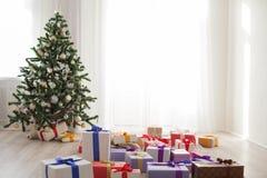 Porciones del árbol de navidad de regalos en un cuarto brillante Fotografía de archivo