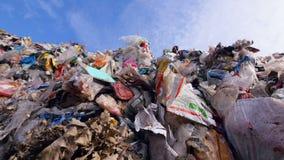 Porciones del plástico, basura inútil en el landfillsite Descarga urbana de la basura del bramido almacen de metraje de vídeo