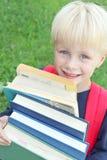 Porciones que llevan del pequeño niño de libros de escuela pesados grandes Imagen de archivo libre de regalías