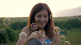 Porciones que soplan divertidas de la mujer joven de burbujas de jabón en la puesta del sol almacen de metraje de vídeo