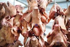 Porcs principaux accrochant sur des crochets Photos stock