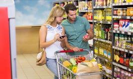 Porducts de nourriture de couples lumineux et carnet de achat d'utilisation Photos stock