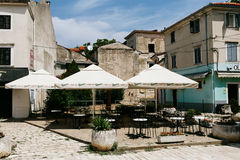 Porec, Croatia - July, 2016 - Empty tables of European cafe on a street in the historic center of Porec, Croatia Royalty Free Stock Image