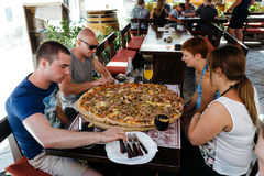 Porec, Croatia - July, 2016 - Group of people eat a large pizza at the legendary stari saloon Stock Photo