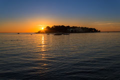 Porec - Croatia sunset at the seaside. Sunset in Croatia during a summer vacation at the beach. Beatiful golden hour, with the sun setting behind an island Royalty Free Stock Images