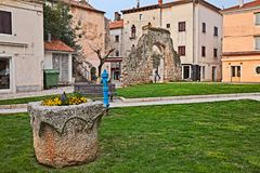 Porec, Istria, Croatia: picturesque corner in the old town. With a large stone pot and the remains of an ancient arch stock photo