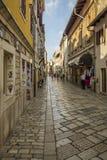 POREC, KROATIEN, AM 24. SEPTEMBER 2017: Tourist, der die alte Straße von Porec besucht und Waren vom Kaufmann kauft Stockbild