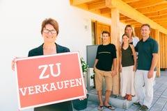 Pośrednik handlu nieruchomościami Z Niemiecką rodziną Sprzedaje Ich dom Zdjęcia Royalty Free