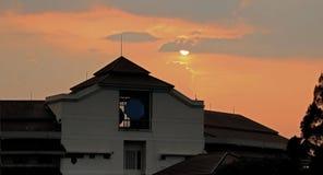 Pores do sol atrás da construção Foto de Stock Royalty Free