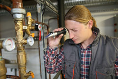 Porfessional plumber controling water quality from heater Royalty Free Stock Images