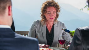 Poring red vine on business meeting. Close-up slow motion footage of a waiter poring the vine in to the glass standing before the beautiful business woman no stock video footage