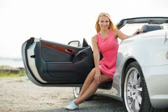Porisng felice della giovane donna in automobile convertibile fotografia stock libera da diritti