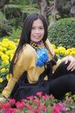 Poritait femelle heureux se reposant dans le domaine de fleur Photo stock
