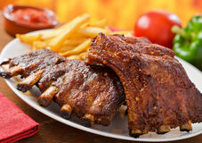 Pork Baby Back Ribs. Two racks of barbecued pork baby back ribs with french fries and dipping sauce Stock Photo