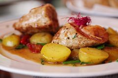 Pork with baked potatoes and vegetables royalty free stock image