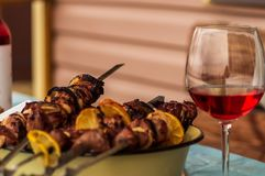 Pork barbecue  on grill with spices, closeup. Hot Pork barbecue  prepared on grill with spices, a glass of wine, closeup Stock Image