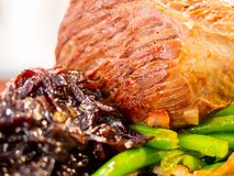 Pork with beans and onion. Closeup of a pork roast with green beans and glazed onion stock images