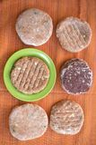 Top view of mixed frozen burgers of beef and pork meat. Pork and beef burgers set on a colored table Royalty Free Stock Image