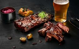 Pork ribs in barbecue sauce and a glass of beer on a black slate dish. A great snack to beer on a dark stone background. Pork and beef ribs in barbecue sauce and stock images
