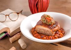 Pork belly with bean stew and mashed vegetables stock images