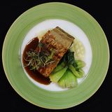 Pork belly crackling with mash potato, saute bok choy and soya sauce stock image