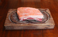 Pork belly raw and salted on a wooden tray. Salted slab of raw pork belly on a wooden tray Royalty Free Stock Photography