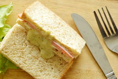 Pork bologna whole wheat sandwich with fork and knife on chop block Royalty Free Stock Photography