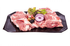 Pork on the bone. Fresh meat with vegetables on white background. Studio photography Royalty Free Stock Images