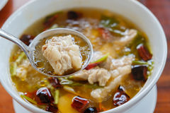 Pork bone hot and sour soup. Scoop pork bone hot and sour soup with spoon in the middle Royalty Free Stock Photo