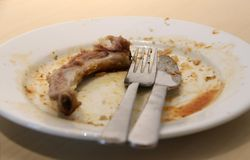 Pork bone with knife and fork in a dish is empty. Eaten plate of food. Pork bone with knife and fork in a dish is empty. Eaten plate of food, pork chop steak on Stock Photography