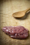 Pork brain. Over wood background with wooden spoon royalty free stock photos