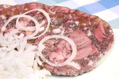 Pork brawn slices with onion on plate Stock Image
