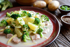 Pork with broccoli, ginger root and boiled potatoes. A plate of pork with broccoli, ginger root and boiled potatoes on a wooden background stock image