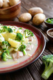 Pork with broccoli, ginger root and boiled potatoes. A plate of pork with broccoli, ginger root and boiled potatoes on a wooden background royalty free stock photos