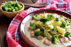 Pork with broccoli, ginger root and boiled potatoes. A plate of pork with broccoli, ginger root and boiled potatoes on a wooden background royalty free stock photography