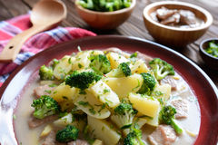 Pork with broccoli, ginger root and boiled potatoes. A plate of pork with broccoli, ginger root and boiled potatoes on a wooden background stock photos