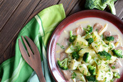 Pork with broccoli, ginger root and boiled potatoes. A plate of pork with broccoli, ginger root and boiled potatoes on a wooden background royalty free stock images